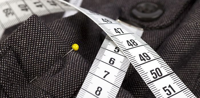 Clothing Alterations: A tape measure draped over a piece of patterned fabric.